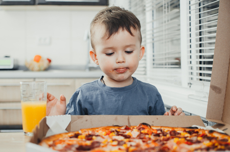 the little boy eats a huge harmful pizza himself in the kitchen and drinks juice, very fat and harmful