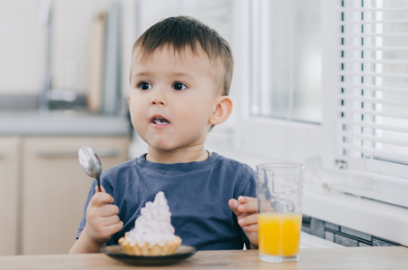 the child in the kitchen eating a cake with cream is very appetizing, spoon Stock Photo
