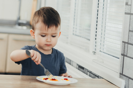 a child in the kitchen eats eggs or omelets in the afternoon Imagens