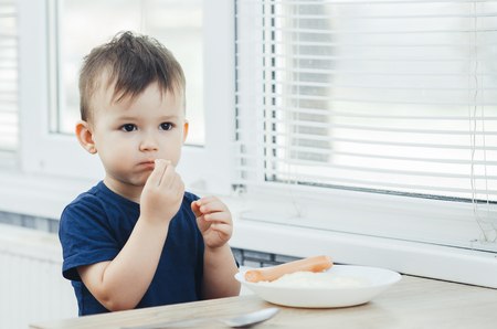 baby eating sausage in the kitchen is very charming and emotional Foto de archivo