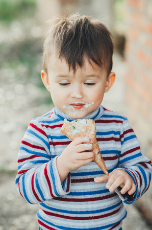 Outdoor portrait of a young boy   eating ice cream