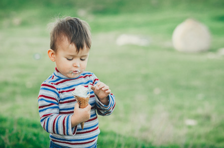 little cute boy eating ice cream three years very appetizing, amid nature, green grass