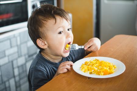 un niño con una camiseta en la cocina comiendo una tortilla, un tenedor Foto de archivo
