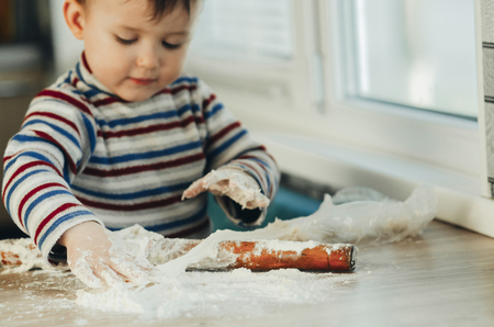 the child makes dough from flour house kitchen, played with the little chef