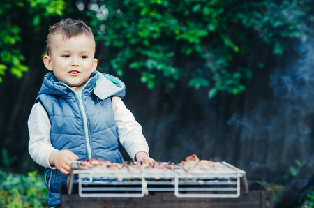 a small child on their own barbecue on the grill helps
