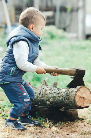 a little kid is chopping a tree, a big axe is dangerous