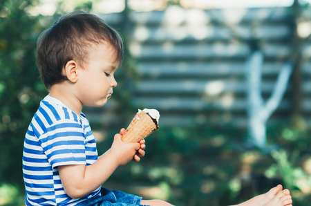 cute little boy in the Park or garden eating ice cream in summer t-shirt Stock Photo