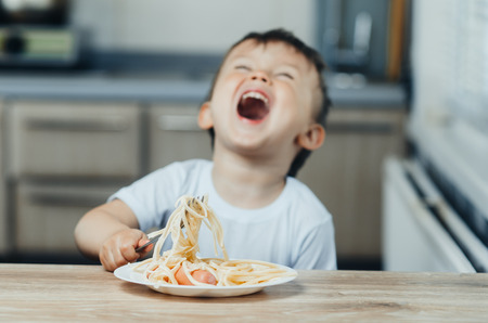 the child eats pasta with a fork and shouts rejoices very much 版權商用圖片