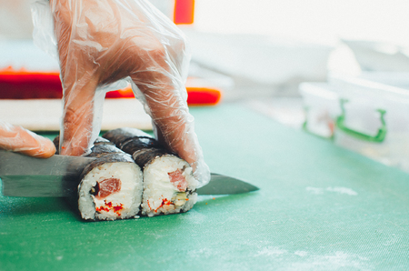 The cook makes a sushi roll with bamboo Mat cuts. The process of cooking sushi roll Фото со стока
