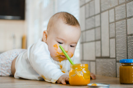 beautiful baby chest all dirty in fruit puree, pumpkin with spoon in hand next to a jar of food Stock Photo