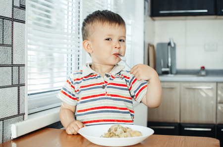the child in the kitchen with a fork eating young potatoes