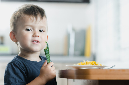 the child in the kitchen eating fresh cucumber and omelet