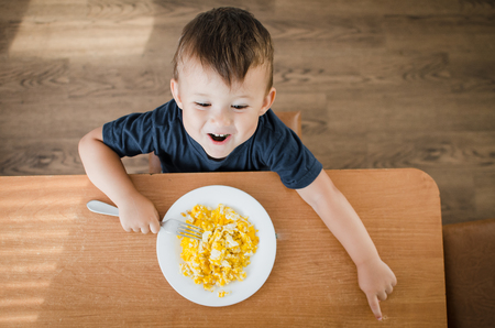 the child eagerly in the kitchen eating scrambled eggs, day, the view from the top