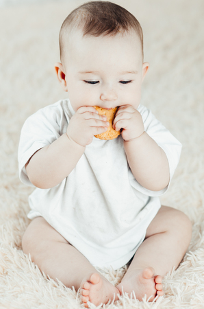 charming breast child sits and licks biscuits, scratching his teeth