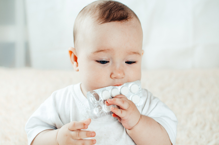Baby chest plays with pills on the bed, tries, sticks in the mouth
