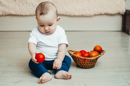 little baby girl sitting on the floor and playing with tomatoes Banco de Imagens - 105345318