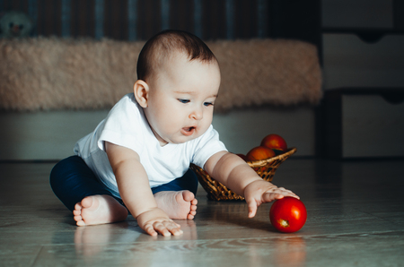 little baby girl sitting on the floor and playing with tomatoes
