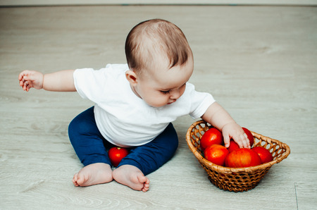 little baby girl sitting on the floor and playing with tomatoes Banco de Imagens - 105345450