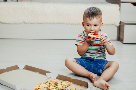 the child sits on the floor and eats pizza very appetizing and greedy, in shorts and a t-shirt