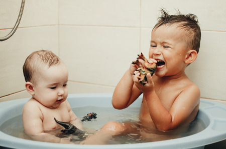 children, brother and sister in the bathroom swimming, playing splashing