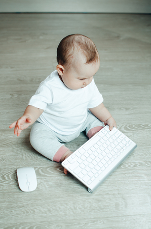 A small child typing, sitting on the floor playing with the keyboard and mouse