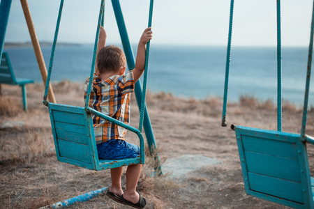 Baby on swing swinging one near the sea, in shirt and denim shorts Foto de archivo