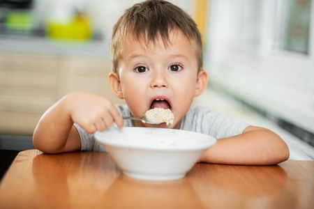 a charming child in a t-shirt in the kitchen eats oatmeal very greedily Imagens
