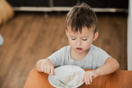 a charming child in a t-shirt in the kitchen eats oatmeal very greedily Stock fotó