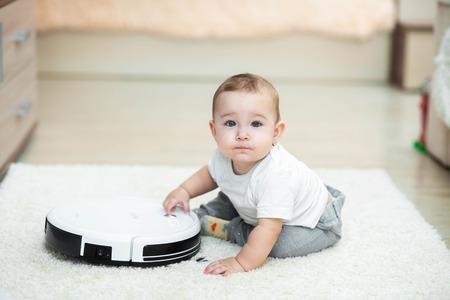 Robotic vacuum cleaner on the carpet, next to the baby girl