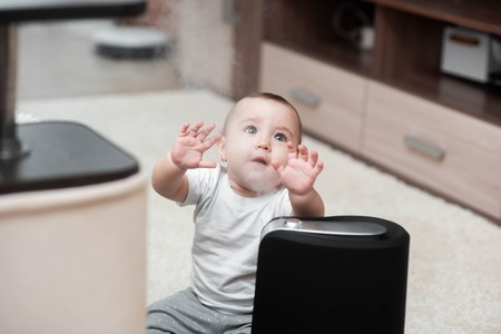 Little baby looks at the humidifier. Moisture in the house concept