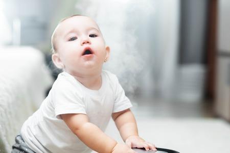 Kleines Baby schaut auf den Luftbefeuchter. Feuchtigkeit im Hauskonzept