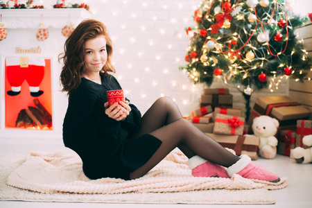 Cute girl sitting on the carpet against the Christmas tree and fireplace in a cozy sweater in the hands of a mug