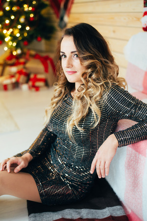 Beautiful girl in evening dress sitting on the background of Christmas decorations