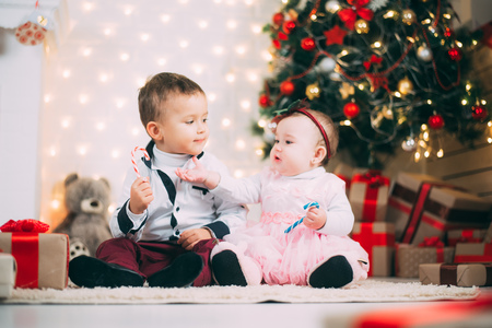 small children near the Christmas tree and fireplace with colored candies in their hands 写真素材