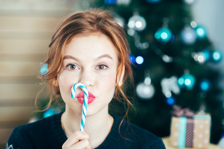 portrait of beautiful girl with candy cane near face on Christmas tree background