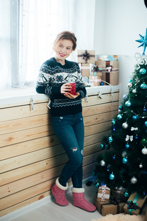 girl with a red mug in her hands near the window, on the background of a Christmas tree 写真素材