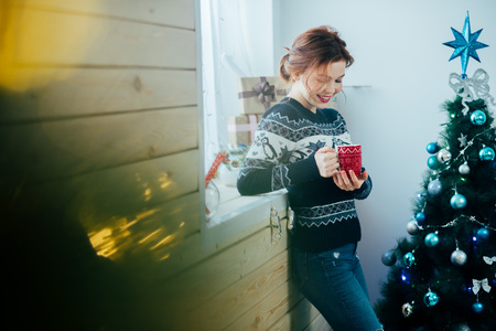 girl with a red mug in her hands near the window, on the background of a Christmas tree Zdjęcie Seryjne