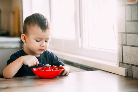 A child in the kitchen eating their own oatmeal with a red plate