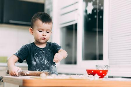 The child makes dough dumplings or dumplings is fun with enthusiasm