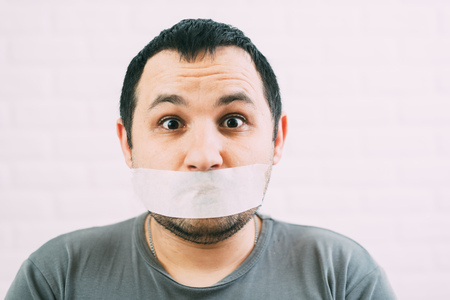 Angry man mouth covered by masking tape Stockfoto