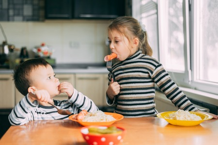 Children eat pasta and sausage in the kitchen