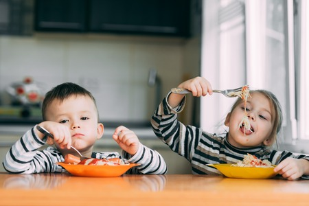 Boy and girl in the kitchen eating pasta Reklamní fotografie