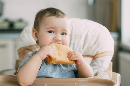 baby in the kitchen in the high chair there is a piece of bread