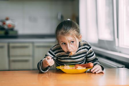 Mädchen isst Nudeln mit Wurst in der Küche in einer gestreiften Jacke eating Standard-Bild