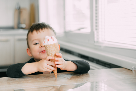 A child in a dark-blue t-shirt in the bright kitchen eating a waffle ice cream cone in the summer house