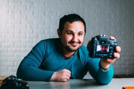 un hombre con barba se toma una selfie con una cámara SLR grande