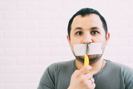 Angry man, mouth covered with duct tape cuts with a stationery knife