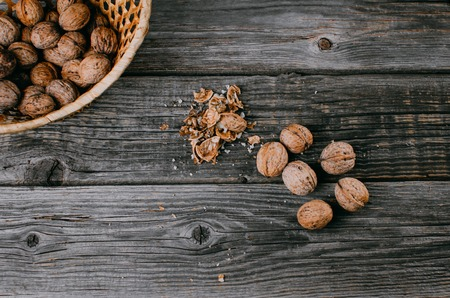 lots of nuts and a basket of nuts on the wooden table Imagens