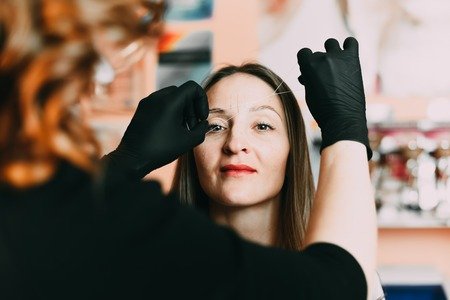 Cosmetologist client plucks eyebrows thread before the procedure microbleeding Stock Photo