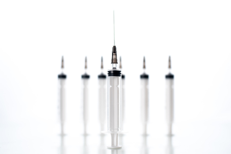 on white background with reflection are syringes in the blur in the foreground one syringe